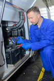 Mechanic fixing jump start cables to battery bus. Mechanic fixing jump start cables to battery of bus Stock Photography