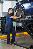 Mechanic Fixing Lifted Car Royalty Free Stock Image