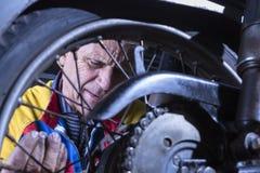 Mechanic fixing a motorbike wheel Royalty Free Stock Image