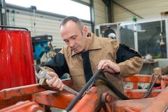 Mechanic fixing plow on tractor. Mechanic fixing plow on the tractor royalty free stock images