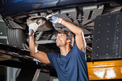 Mechanic Fixing Underneath Car. Smiling male mechanic fixing underneath lifted car at garage stock photography