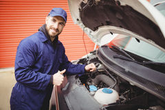Mechanic fixing  a van. With thumbs up Royalty Free Stock Photography