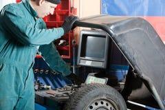 Mechanic in garage. Mechanic changing car tire in garage stock images