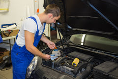 Mechanic in garage checking motor oil level at a car royalty free stock images