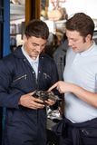 Mechanic In Garage Helping Apprentice To Fix Car Engine stock photo