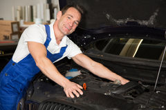 Mechanic in garage repairing car Stock Photo