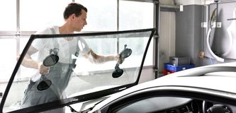 Mechanic in a garage replaces defective windshield of a car. Closeup stock images