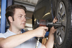 Mechanic In Garage Using Air Hammer On Car Wheel Stock Photography