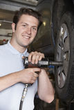 Mechanic In Garage Using Air Hammer On Car Wheel Royalty Free Stock Photography