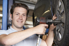 Mechanic In Garage Using Air Hammer On Car Wheel Royalty Free Stock Image