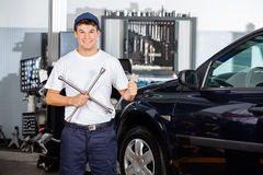 Mechanic Gesturing Thumbs Up While Holding Rim Wrench Royalty Free Stock Photography