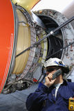 Mechanic with giant jet engine Stock Image