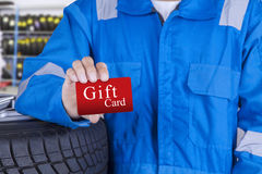 Mechanic with a gift card. Mechanic person standing in the workshop while showing a gift card Royalty Free Stock Photography