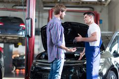 Mechanic giving client keys Royalty Free Stock Images