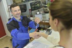 Mechanic giving key to his customer Royalty Free Stock Image