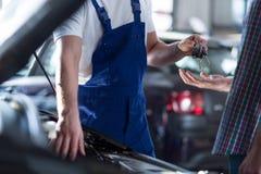 Mechanic giving keys Stock Images
