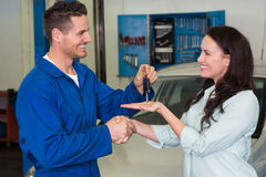 Mechanic giving keys to satisfied customer. At the repair garage Royalty Free Stock Photo
