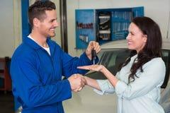 Mechanic giving keys to satisfied customer. At the repair garage royalty free stock photo