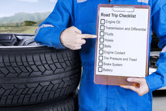 Mechanic giving road trip tips. Close up of a male mechanic showing and pointing a road trip tips on the clipboard next to a pile of tires Stock Photo