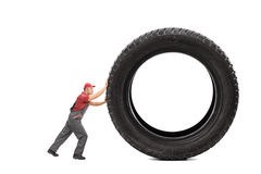 Mechanic in a gray jumpsuit pushing a giant black tire Stock Image