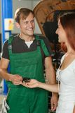 The mechanic in green overalls gives the beautiful girl in a whi royalty free stock photos