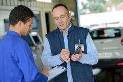 Mechanic guiding apprentice on making estimates Stock Images