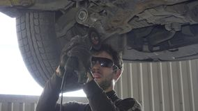 Mechanic guy with glasses cutting worn automobile part with grinder in garage stock video footage