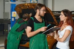 A mechanic guy in a green suit tries to repair the engine of the royalty free stock photo