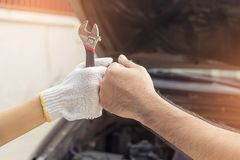 Mechanic hand checking and fixing a broken car in  garage.hand o Royalty Free Stock Photos