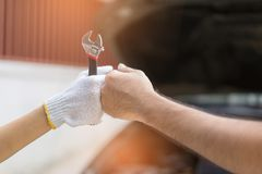 Mechanic hand checking and fixing a broken car in  garage.hand o Stock Photo