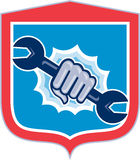 Mechanic Hand Holding Spanner Shield Punching Stock Image