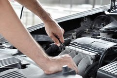 Mechanic hand holding wrench checking car engine Royalty Free Stock Images