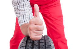 Mechanic hand on tire showing like or thumb-up Stock Images