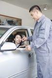 Mechanic Handing Keys to Businesswoman sitting in Car stock photo