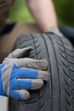 Mechanic hands and car tire Royalty Free Stock Photo
