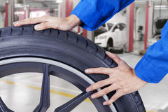 Mechanic hands pushing tire at workshop Stock Photography