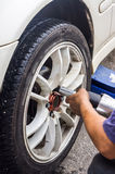 Mechanic hands with tool changing tyre of car. Detail image of mechanic hands with tool, changing tyre of car, with blurred background of garage. Soft focus with Royalty Free Stock Image