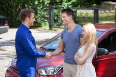 Mechanic handshaking with couple by car Royalty Free Stock Photography