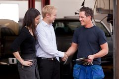 Mechanic with Happy Customer. A happy attractive mechanic shaking hands with a customer couple,happy with their service stock images