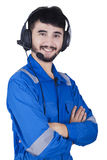 Mechanic with headset and smiling in studio. Young mechanic wearing uniform and using headset to work as customer service,  on white background Royalty Free Stock Images