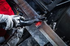 Mechanic heats the metal. Close-up of a male mechanic in red uniform and protective gloves heats the metal by an induction machine in the workshop. Heating of Stock Photo