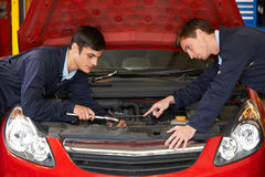Mechanic Helping Trainee To Fix Engine Royalty Free Stock Image