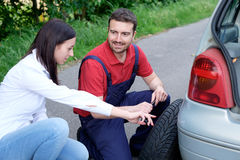 Mechanic helping young woman Royalty Free Stock Image