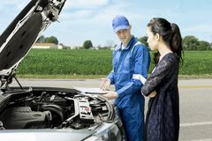 Mechanic and his client with repair cost Royalty Free Stock Photography