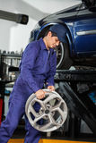 Mechanic Holding Alloy At Repair Shop Stock Images