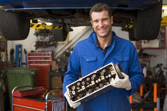 Mechanic holding car part smiling Stock Images