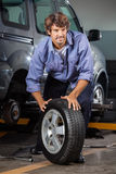 Mechanic Holding Car Tire Royalty Free Stock Images