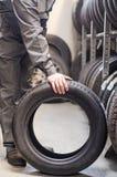 Mechanic holding car tire. Stock Image