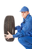 Mechanic is holding car tire on white background Stock Image