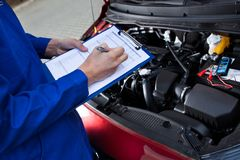 Mechanic holding clipboard in front of open car engine Royalty Free Stock Photo